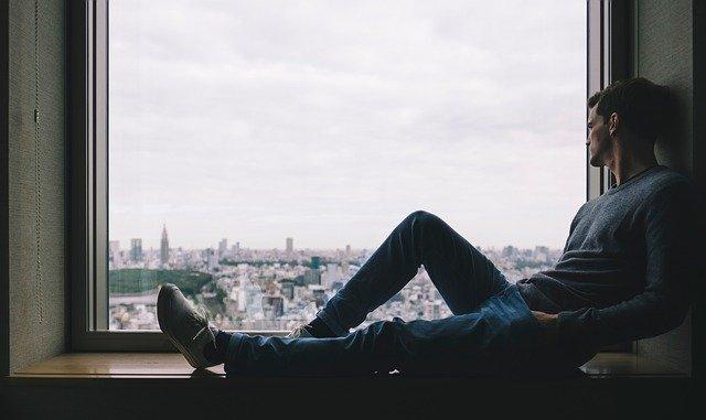 Muž sediaci pri okne s výhľadom na mesto.jpg