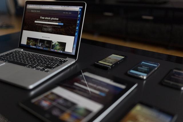 Notebook, tri mobily a tablet na čiernom stole