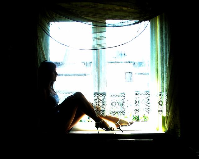 Žena sedí pri okne