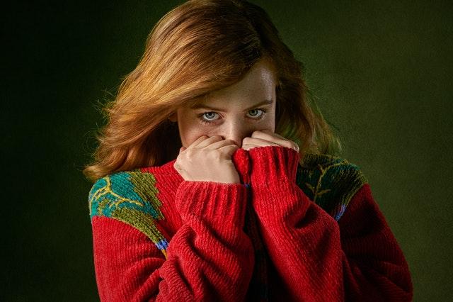 Žena v červenom svetri si zakrýva tvár